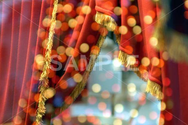 赤いドレープカーテンとガラスに反射したイルミネーションのイメージ写真