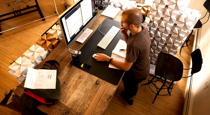 立ち姿勢でパソコン作業をする男性
